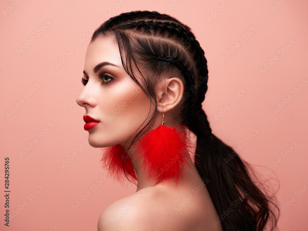 Fototapeta Brunette girl with perfect makeup. Beautiful model woman with curly hairstyle. Care and beauty hair products. Lady with braided hair. Model with jewelry. Pink background
