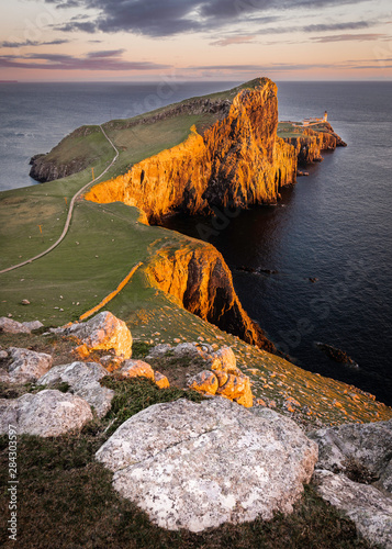 Fototapeta Neist Point, famous landmark with lighthouse on Isle of Skye, Scotland lit by setting sun
