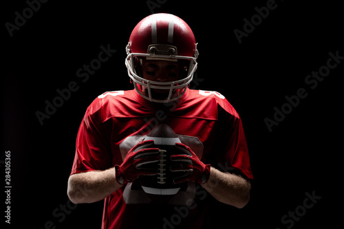 American football player standing with rugby helmet and ball Fototapet