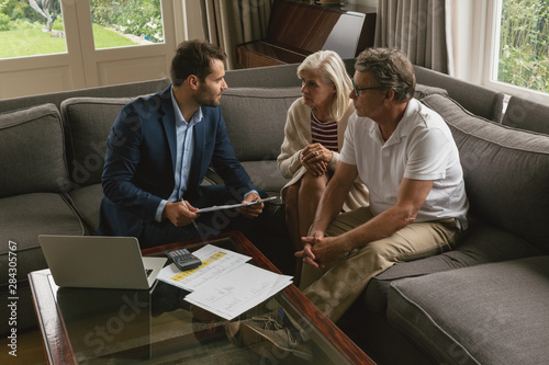 Fotografía  Active senior couple discussing with real estate agent in living room