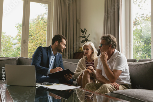 Fotografía  Active senior couple discussing with real estate agent over documents in living