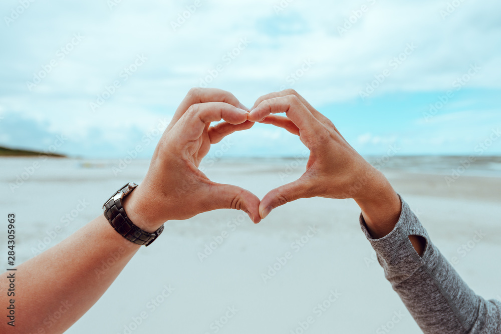 Fototapety, obrazy: hands of a woman and a man forming a heart shape against a cloudy summer sky
