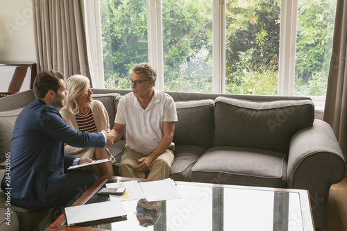 Fotografía  Active senior man shaking hands with real estate agent in living room