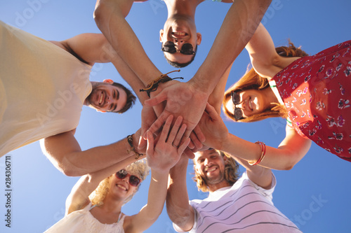 Group of friends forming hand stack on the beach