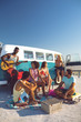 canvas print picture - Group of friends having fun near camper van at beach