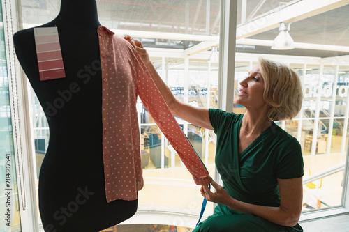 Fototapeta  Female fashion designer using measuring tape on a mannequin in design studio