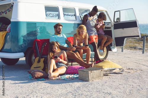 Fotografia  Group of friends using mobile phone near camper van at beach