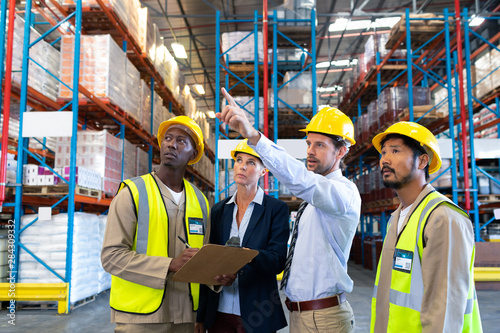 Male supervisor standing with coworkers and pointing at distance in warehouse Fototapeta
