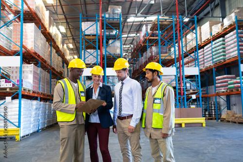 Obraz na płótnie Diverse staffs working together on clipboard in warehouse