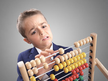 Young Boy Accountant Businessman Does Calculation On A Abacus