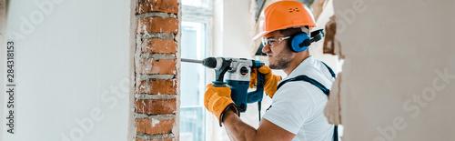 Obraz panoramic shot of handyman in uniform and yellow gloves using hammer drill - fototapety do salonu