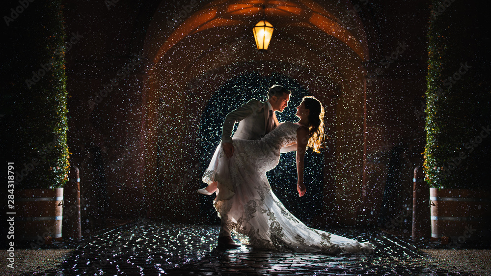 Fototapety, obrazy: a bride and groom is dancing happily in the rain