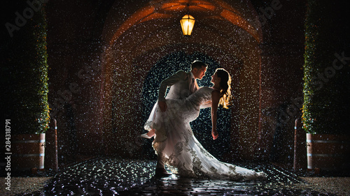 a-bride-and-groom-is-dancing-happily-in-the-rain