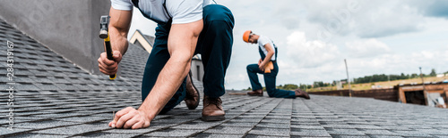 Canvas Print panoramic shot of handyman holding hammer while repairing roof near coworker