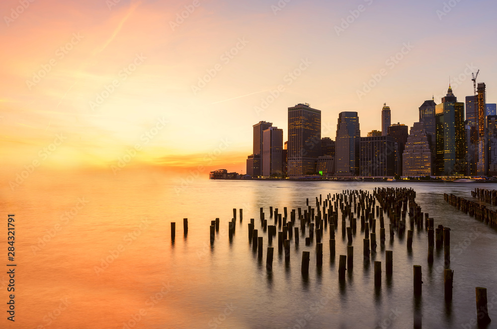 Fototapety, obrazy: View from the water of the bay on the night city center of New York at sunset. Skyscrapers glowing in the dark against the sunset sky.