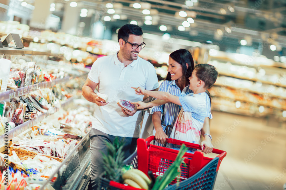 Fototapeta Happy family with child and shopping cart buying food at grocery store or supermarket
