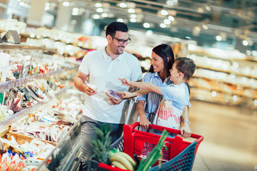 Szczęśliwa rodzina z dzieckiem i wózek na zakupy kupuje jedzenie w sklepie spożywczym lub supermarkecie