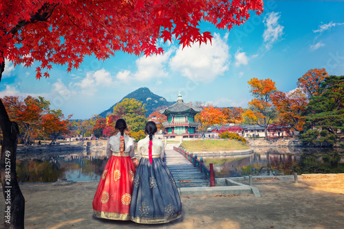 Fotobehang Kersenbloesem young woman with umbrella in autumn park Gyeongbokgung palace, Hyangwonjeong Pavilion, in autumn Seoul,South Korea.