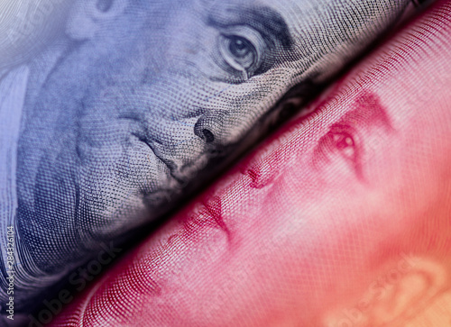 Fototapeta Face to face of Benjamin Franklin and Mao Tse tung from US dollar and China Yuan banknote