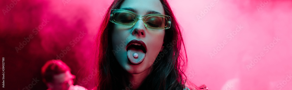 Fototapeta panoramic shot of beautiful girl in sunglasses with lsd on tongue in nightclub with pink smoke