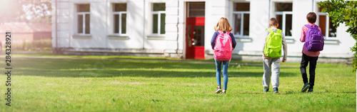 Pinturas sobre lienzo  Children with rucksacks standing in the park near school