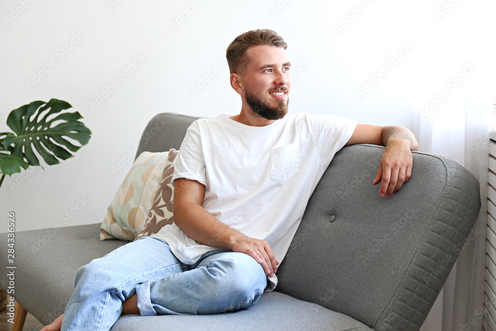 Fototapeta Bearded guy wearing blank white t-shirt & denim pants sitting alone at home on grey textile couch. Young man w/ facial hair in domestic situations. Interior background, copy space, close up, monstera.