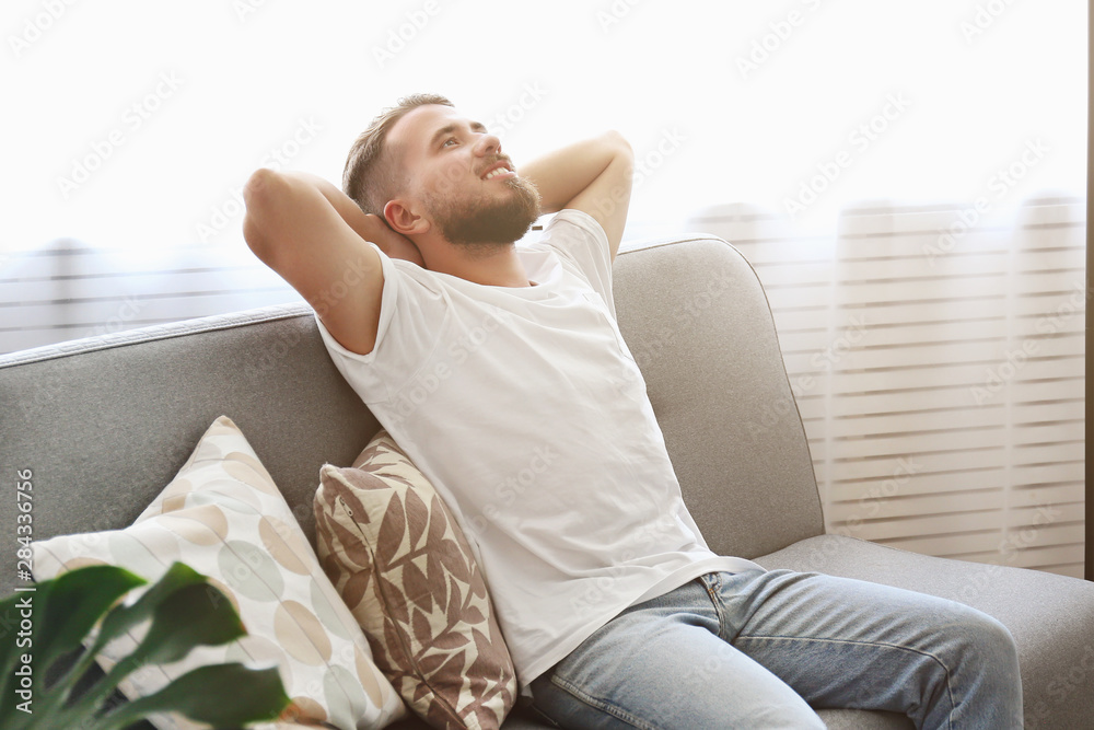 Fototapety, obrazy: Bearded guy wearing blank white t-shirt & denim pants sitting alone at home on grey textile couch. Young man w/ facial hair in domestic situations. Interior background, copy space, close up, monstera.