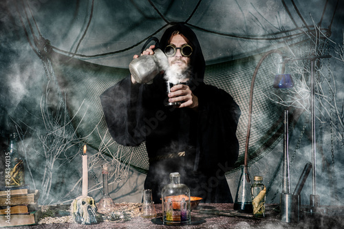 The medieval alchemist make magic ritual at the table in his smoke laboratory Wallpaper Mural