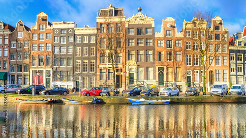 Fototapeta Amsterdam  cityscape-on-a-sunny-winter-day-view-of-the-houses-and-the-city-channel-with-boats-in-the-historic-center-of-amsterdam-the-netherlands