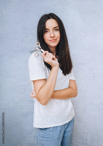 A young girl hairdresser holds two scissors and smiles while standing against a gray background. The concept of creating haircuts.