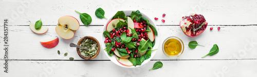 Obraz na plátně Spinach, apple salad with pomegranate seeds