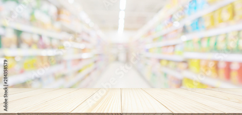 Fotografía Empty wood table top with abstract supermarket grocery store aisle blurred defoc