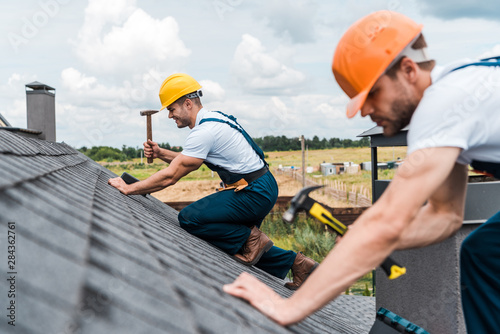 selective focus of handsome handyman repairing roof with colleague Fototapet