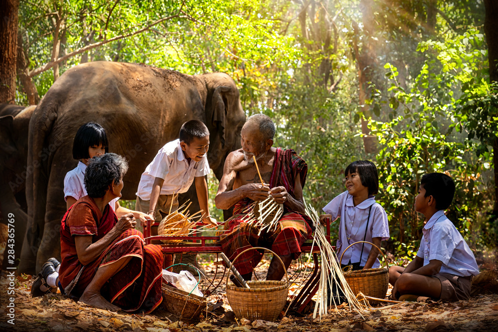 Fototapeta Senior Men and women are weaves basket with nephew and granddaughter and a big elephant in the forest. Old man and woman weaves bamboo basket or fish trap with elephant in forest. Surin, Thailand.