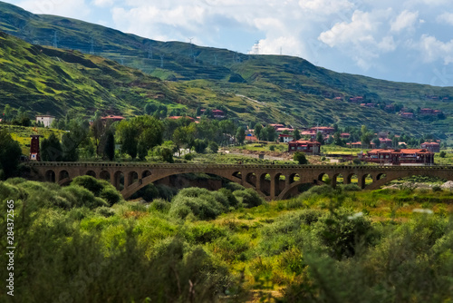 Spoed Fotobehang Rijstvelden Village and bridge across the river in the mountain, Luhuo, Garze Tibetan Autonomous Prefecture, western Sichuan, China