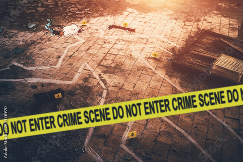 Fotografia White chalk outline of killed body, blood an floor and yellow police caution tape with text - crime scene, do not enter