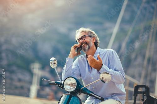 Fotografiet  Mature man on motor scooter using phone in marina.