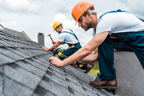 Obraz selective focus of handsome handyman repairing roof with coworker - fototapety do salonu