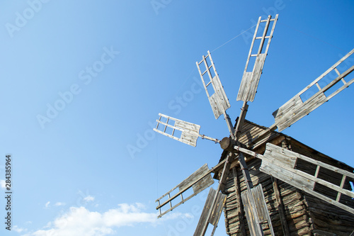Old wooden windmill against a blue sky Canvas Print