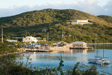 Vieques, Puerto Rico - A Seaside Marina Is Set In The Waters Of A Calm Ocean Bay. In The Foreground A Sailboat Can Be Seen Anchored In The Bay.