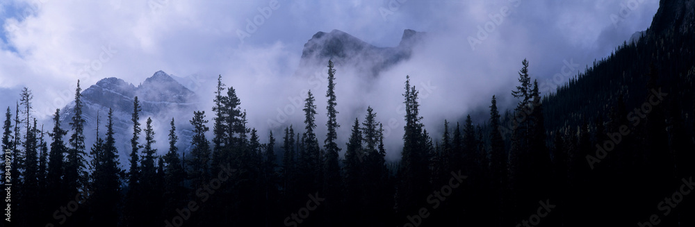 Fototapeta Canada, Alberta, Banff NP. Clouds swirl around mountain peaks above Lake Louise Junction in Banff NP, a World Heritage Site, Alberta, Canada.