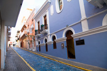 San Juan, Puerto Rico - Two People Are Walking Up A Sloped Brick Lane In An Old World Section Of The City. The Brick Road Is Painted Blue.