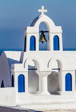 Oia, Greece. Greek Orthodox Church Steeple, Cross, Bell, And Blue Arches Against Aegean Sea