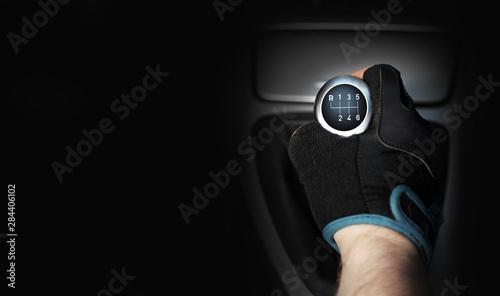 Obraz Dłoń w rękawiczce na sześcio biegowej dźwigni zmiany biegów w samochodzie osobowym, tekst. - fototapety do salonu