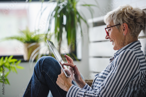 Fotografia  Senior woman using digital tablet at home