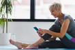 canvas print picture Senior woman using smartphone at home after exercise. The use of technology by the elderly.