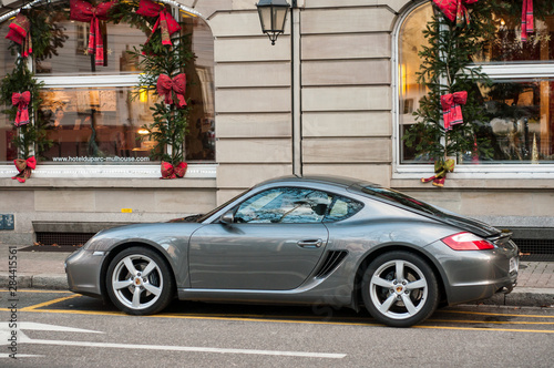 Leinwand Poster Grey porsche 911 parked in the street in front of luxury hotel