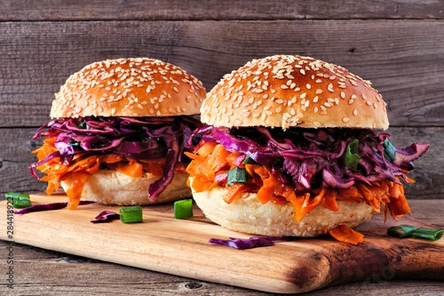 Pulled carrot meatless burgers with red cabbage slaw against a wood background. Healthy eating, plant-based meat substitute concept.