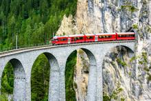 Landwasser Viaduct In Filisur, Switzerland. It Is Famous Landmark Of Swiss Alps. Red Express Train Runs From Mountain Tunnel On High Bridge. Scenic Aerial View Of Amazing Railway In Summer.