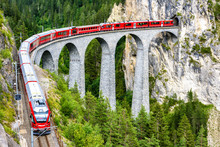 Landwasser Viaduct In Filisur, Switzerland. It Is Famous Landmark Of Swiss. Red Express Train On High Bridge In Mountains. Scenic View Of Amazing Railway In Summer. Concept Of Travel In Alpine Europe.